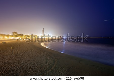 Glow from the city at night illuminates the sky and sea at Icaria beach in Barcelona, Catalonia, Spain. - stock photo