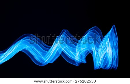 Glowing abstract curved lines. Blue colors. Black background. Done by long exposure technique - stock photo