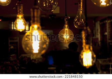 glowing and broken tungsten lamps, heated filament light bulb, incandescent illumination on dark background - stock photo
