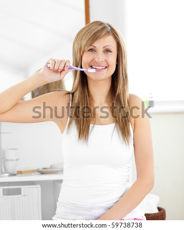 Glowing blond woman brushing her teeth in the bathroom at home