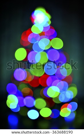 glowing blur christmas tree on  dark background - stock photo