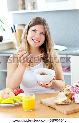 Glowing brunette woman eating cereals with raspberries sitting at the breakfast table in the kitchen