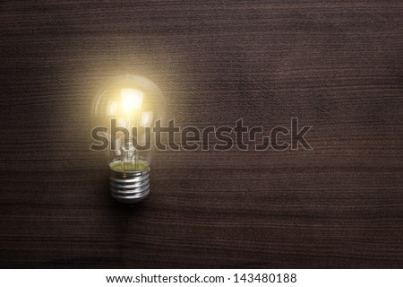 glowing bulb on the brown wooden background - stock photo