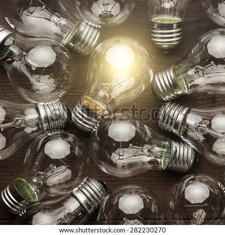 glowing bulb uniqueness concept. many bulbs on brown wooden table - stock photo