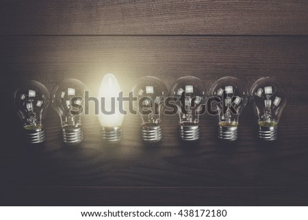 glowing bulb uniqueness concept on brown woodentable - stock photo