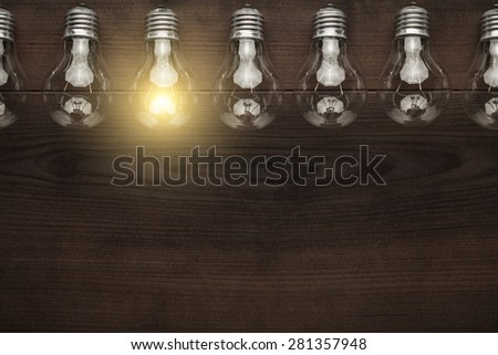 glowing bulb uniqueness concept with copy space on brown wooden table - stock photo