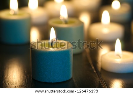 Glowing, Burning Candles in Spa, Religious, Romantic or Holiday Setting with Blurred Background - stock photo