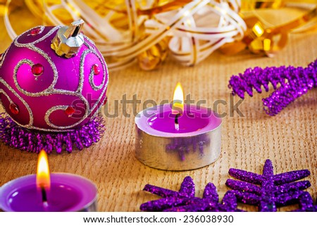 glowing candles and christmas ball on wooden board - stock photo