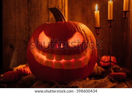 Glowing carved pumpkin or jack-o-lantern for Halloween in rustic setting with candles - stock photo