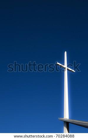 Glowing cross on deep blue sky - stock photo