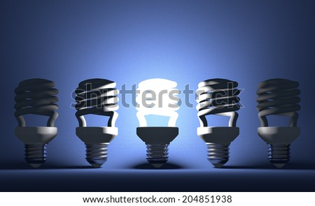 Glowing fluorescent light bulb among switched off ones on blue textured background - stock photo