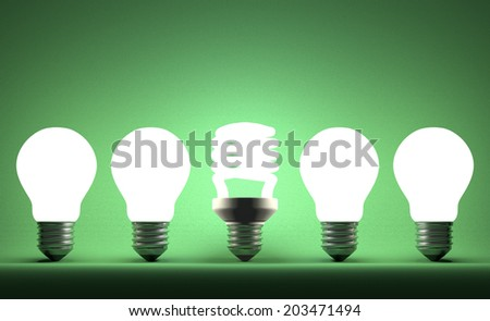 Glowing fluorescent light bulb in row of incandescent ones on green textured background