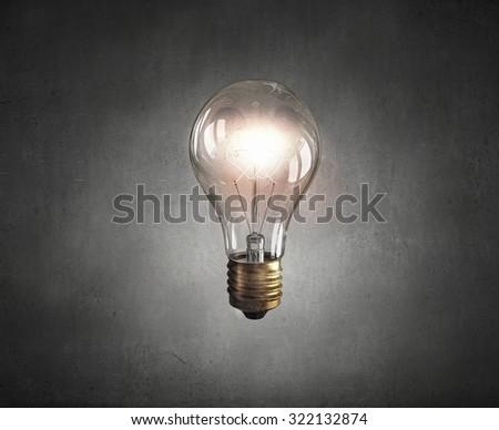 Glowing glass light bulb on dark background - stock photo