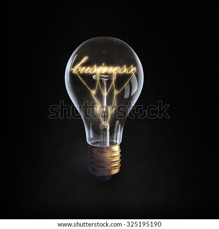 Glowing glass light bulb with business word inside