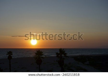Glowing gold colors of ocean sunset lights above Channel Islands and Mandalay Beach, Oxnard, California - stock photo