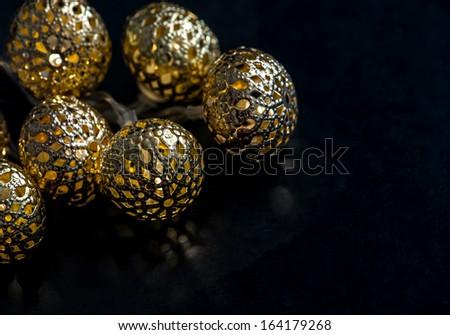 Glowing golden lights garland on dark background. Selective focus - stock photo