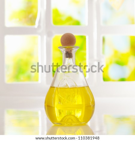 Glowing golden olive oil in a stoppered glass container for dispensing for cooking or as a salad dressing backlit by a bright airy window - stock photo