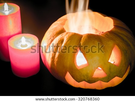 Glowing halloween pumpkin in candlelight - stock photo