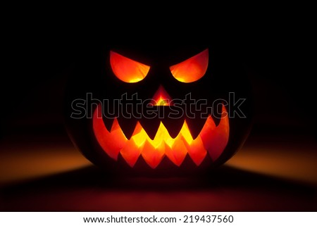 Glowing halloween pumpkin in dark - stock photo