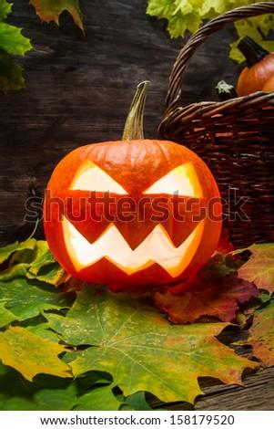 Glowing halloween pumpkin on leaves - stock photo