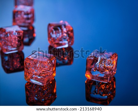 Glowing ice cubes on blue reflective surface - stock photo