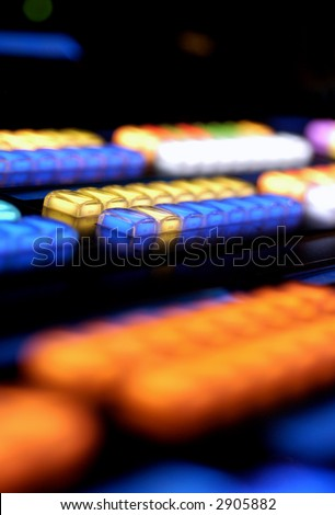Glowing keys on a media console in a dark room vertical (SHALLOW DOF) - stock photo