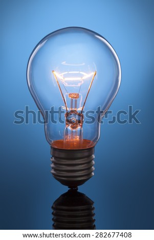 glowing lamp on blue background - stock photo