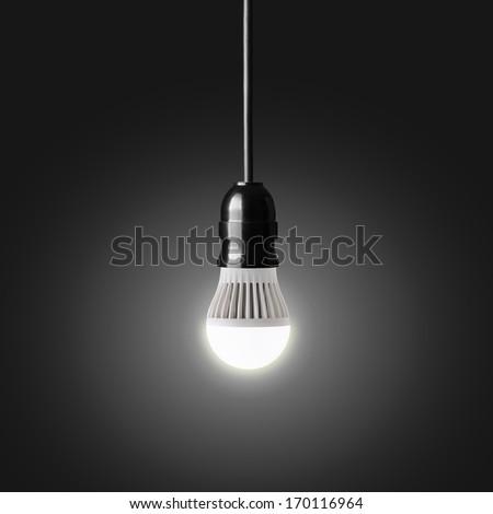 Glowing LED bulb on black - stock photo