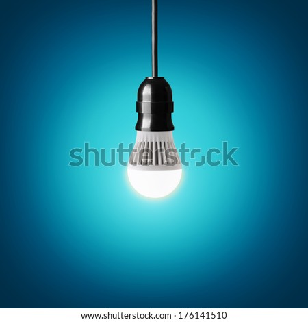 Glowing led bulb on blue background - stock photo
