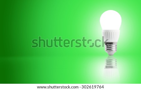 Glowing LED energy saving bulb on a green background - stock photo