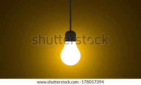 Glowing light bulb in lamp socket hanging on wire on dark yellow textured background