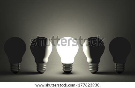 Glowing light bulb in row of switched off ones on dark gray textured background. Front view