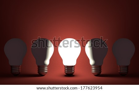 Glowing light bulb in row of switched off ones on dark red textured background. Front view
