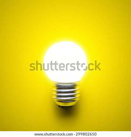 Glowing light bulb isolated on yellow background - stock photo