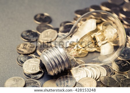 Glowing light bulb on many coins - stock photo