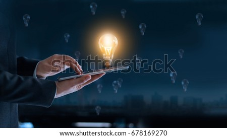 Glowing light bulb over laptop of businessman among the others that not bright, it's symbolic of creative and bright idea or leadership, innovation and creativity concept