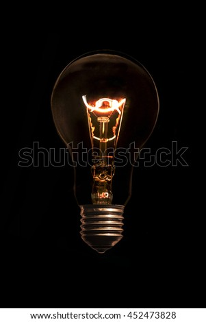 Glowing light bulb without wires on black background