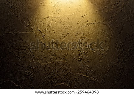 Glowing light illuminating a rough textured wall from above in the darkness, conceptual background - stock photo