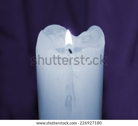 Glowing mourning candle in darkness taken closeup on purple. - stock photo