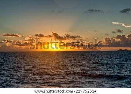 Glowing orange sunset over the ocean as the orb of the sun dips below the horizon at twilight, beauty in nature background - stock photo