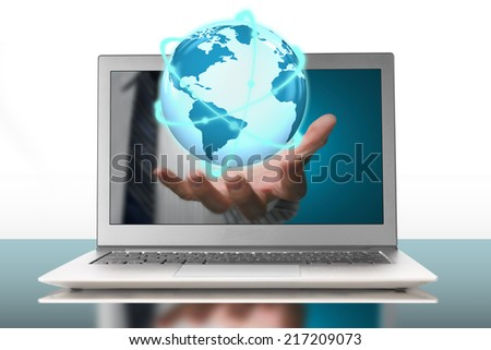 glowing orbit globe in plam through laptop on white background