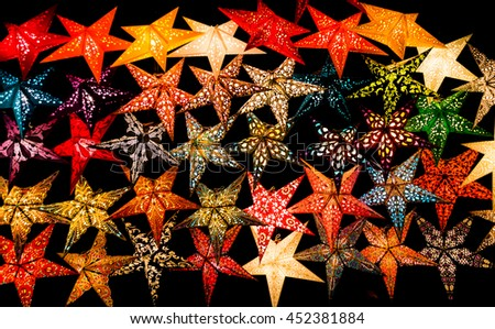 Glowing Paper Star Christmas Decorations in Black Background