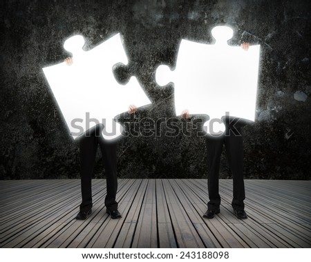 Glowing puzzles businessmen hold to connect illuminating the dark and wooden floor - stock photo