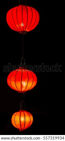 Glowing red Chinese lanterns on a black background.