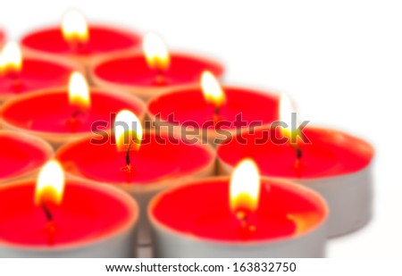 Glowing red tea lights on white - stock photo