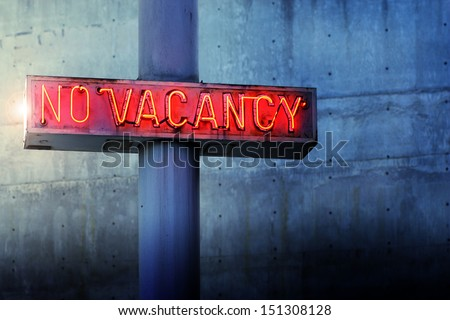 Glowing retro neon 'no vacancy' sign against cool blue wall background - stock photo