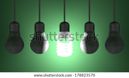 Glowing spiral light bulb among dead tungsten ones in lamp sockets hanging on dark green textured background - stock photo