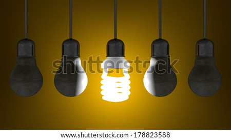 Glowing spiral light bulb among dead tungsten ones in lamp sockets hanging on dark yellow textured background - stock photo