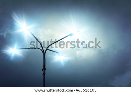 Glowing street lamp on a background of blue sky overcast cloudy