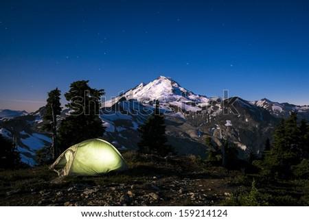 Glowing tent beneath moonlit Mount Baker, Washington state Cascades - stock photo